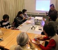 女性講師(右上)が、画面を確認しながら、写真を加工して保存する方法を丁寧に教えていた=東京都世田谷区で