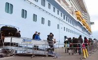 This partially retouched photo taken on Jan. 10, 2019 shows foreign tourists disembarking from a cruise ship moored at the port of Hakata in the southern Japan city of Fukuoka. (Mainichi/Kenta Miyahara)