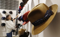 A woman looks at hats in a Borsalino store in downtown Milan, Italy, on Jan. 16, 2019. (AP Photo/Antonio Calanni)