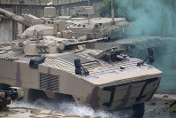 Soldiers in an armored personnel carrier roar through a military demonstration at the International Defense Exhibition and Conference in Abu Dhabi, United Arab Emirates, on Feb. 17, 2019. (AP Photo/Jon Gambrell)