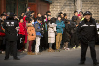In this Jan. 1, 2016 file photo, Chinese policemen watch as depositors from Ezubao gather outside the State Bureau for Letters and Calls Reception Division office in Beijing. (AP Photo/Mark Schiefelbein)