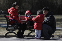 In this Feb. 17, 2019, photo, a couple spend time with their children at a park in Beijing. (AP Photo/Andy Wong)