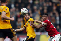 Wolverhampton's Joao Moutinho fights for the ball with Bristol City's Niclas Eliasson, right, during the English FA Cup fifth round soccer match between Bristol City and Wolverhampton Wanderers at Ashton Gate stadium in Bristol, England, on Feb. 17, 2019. (AP Photo/Frank Augstein)