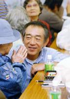 仮設住宅の元住民たちと再会し、笑顔を見せる牧秀一さん=神戸市東灘区で2004年10月、三村政司撮影