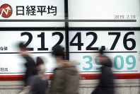 People walk past an electronic stock board showing Japan's Nikkei 225 index at a securities firm in Tokyo, on Feb. 19, 2019. (AP Photo/Eugene Hoshiko)