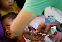 In this Feb. 16, 2019 file photo, Philippine National Red Cross and Health Department volunteers conduct house-to-house measles vaccination to children at an informal settlers community in Manila, Philippines. (AP Photo/Bullit Marquez)
