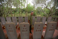 In this Feb. 16, 2019 photo, war veteran Duong Van Dau walks in between a row of headstones at a memorial for North Korean fallen pilots in Bac Giang province, Vietnam. (AP Photo/Hau Dinh)