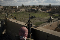 A U.S.-backed Syrian Democratic Forces (SDF) fighter stands atop a building used as a temporary base near the last land still held by Islamic State militants in Baghouz, Syria, on Feb. 18, 2019. (AP Photo/Felipe Dana)