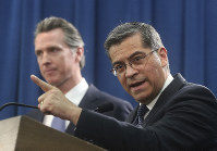 In this Feb. 15, 2019 file photo, California Attorney General Xavier Becerra, right, accompanied by Gov. Gavin Newsom, said California was probably suing U.S. President Donald Trump over his emergency declaration to fund a wall on the U.S.-Mexico border, in Sacramento, California. (AP Photo/Rich Pedroncelli)