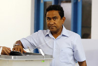 In this Sept. 23, 2018 file photo, then Maldivian President Yameen Abdul Gayoom, right, casts his vote at a polling station during a presidential election day in Male, Maldives. (AP Photo/Eranga Jayawardena)