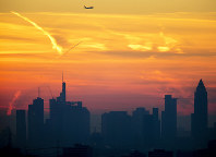 A plane flies over the banking district during sunrise in Frankfurt, Germany, on Feb. 16, 2019. (AP Photo/Michael Probst)