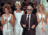 In this October 19, 1995 file photo, German designer Karl Lagerfeld joins models, from left, American Cindy Crawford, Canadian Linda Evangelista and Claudia Schiffer of Germany after the presentation of his 1996 spring-summer ready-to-wear fashion collection for Chanel in Paris. (AP Photo/Remy de la Mauviniere)
