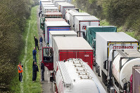 In this April 6, 2016 file photo, truck drivers stand among trucks on the highway from Brussels to Luxembourg, in Spontin, Belgium. (AP Photo/Geert Vanden Wijngaert)