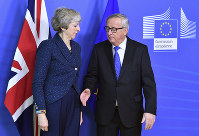 In this Feb. 7, 2019 photo European Commission President Jean-Claude Juncker, right, prepares to shake hands with British Prime Minister Theresa May, left, before their meeting at the European Commission headquarters in Brussels, Belgium. (AP Photo/Geert Vanden Wijngaert)