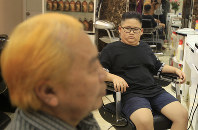 Le Phuc Hai, 66, left, and To Gia Huy, 9, sit after having Trump and Kim haircuts in Hanoi, Vietnam, on Feb.19, 2019. (AP Photo/Hau Dinh)