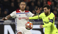 Lyon forward Memphis Depay, left, challenges Barcelona forward Lionel Messi, right, during the Champions League round of 16 first leg soccer match between Lyon and FC Barcelona in Decines, near Lyon, central France, on Feb. 19, 2019. (AP Photo/Laurent Cipriani)