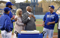 In this June 8, 2016, file photo, former Dodgers player Don Newcombe, second from right, reacts as he stands with his wife, Karen, center, manager Dave Roberts, left, Kenley Jansen, second from left, and Joc Pederson, right, as the Dodgers celebrate Newcombe's 90th birthday prior to a baseball game against the Colorado Rockies, in Los Angeles. (AP Photo/Mark J. Terrill)