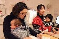 スリングで赤ちゃんを抱っこし、店頭に立つ子連れ出勤のスタッフら=東京都渋谷区のモーハウス青山ショップで