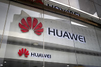 In this Jan. 29, 2019, file photo, the logos of Huawei are displayed at its retail shop window reflecting the Ministry of Foreign Affairs office in Beijing. (AP Photo/Andy Wong)