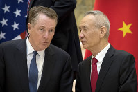 In this Feb. 15, 2019 file photo, Chinese Vice Premier Liu He, right, talks with U.S. Trade Representative Robert Lighthizer, while they line up for a group photo at the Diaoyutai State Guesthouse in Beijing. (AP Photo/Mark Schiefelbein)