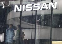 In this Feb. 5, 2019 photo, visitors stand near the logo of Nissan Nissan Motor Co. at its showroom in Tokyo. (AP Photo/Koji Sasahara)