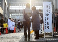 受験のために都立西高校へ入った子供を見つめる保護者=東京都杉並区で2019年2月22日午前7時59分、梅村直承撮影