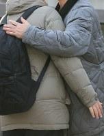 試験が行われる都立西高校の前で子供を抱きしめる保護者=東京都杉並区で2019年2月22日午前7時58分、梅村直承撮影
