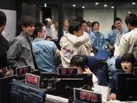 「はやぶさ2」の小惑星「リュウグウ」への着陸が成功し、スタッフと抱き合って喜ぶ津田雄一プロジェクトマネジャー(中央右)=相模原市で2019年2月22日午前7時51分(c)ISAS/JAXA