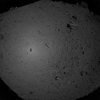 着陸のため降下中の「はやぶさ2」がとらえた小惑星「リュウグウ」。中央左に「はやぶさ2」の影が映っている=JAXA提供
