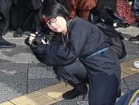 「忍者市駅」の看板の除幕式で、カメラを構える忍者=三重県伊賀市で2019年2月22日、山崎一輝撮影