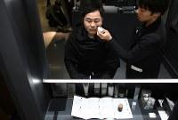 スタッフからメークを施される男性=大阪市北区の阪急メンズ大阪で2019年2月15日、久保玲撮影