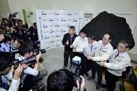はやぶさ2が小惑星リュウグウに着陸したことを受け、同小惑星の模型の前で記念撮影に応じる津田雄一プロジェクトマネジャー(右から2人目)ら=相模原市中央区で2019年2月22日午後0時40分、渡部直樹撮影