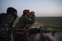 In this Feb. 19, 2019 file photo, U.S.-backed Syrian Democratic Forces fighters watch as an airstrike hits territory still held by Islamic State militants in the desert outside Baghouz, Syria. (AP Photo/Felipe Dana)