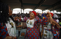In this Feb. 13, 2019 file photo, supporters of incumbent President Muhammadu Buhari sing and dance in advance of his arrival at a campaign rally in Abuja, Nigeria. (AP Photo/Ben Curtis)