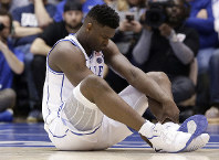 Duke's Zion Williamson sits on the floor following an injury during the first half of an NCAA college basketball game against North Carolina, in Durham, North Carolina, on Feb. 20, 2019. (AP Photo/Gerry Broome)