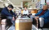 3月一いっぱいで退職することになったことを親しくなった地元住民らに話す藤井宏二医師(左)。理容店の店主、加藤直さん(中央)は「寂しくなる。なんで熱意ある人がこの町を去ってしまうのか」と話した=福島県南相馬市で2019年2月22日午後0時34分、宮武祐希撮影