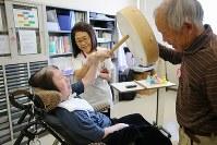 歌や楽器を通じて感覚を刺激する音楽療法で太鼓を叩く久世三枝子さん(左)。健二さんもなじみの歌をいっしょに口ずさんだ=岐阜県美濃加茂市で2018年12月21日、小川昌宏撮影