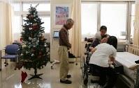車いすに乗せられる三枝子さんを見つめる久世健二さん。病室にはクリスマスツリーが飾られていた=岐阜県美濃加茂市で2018年12月21日、小川昌宏撮影