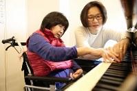 介護付き老人ホーム近くのピアノ教室に通う山口由美子さん。右手だけだがしっかりと鍵盤を抑え、歌った=東京都港区で2018年12月22日、小川昌宏撮影