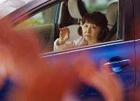 千葉療護センターを退院する山口由美子さん。大勢のスタッフの見送りに、顔を上げ、自分で手を上げて応えた=千葉市美浜区で2017年11月2日、小川昌宏撮影