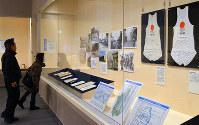 1964年の東京五輪聖火リレーで使われたランナーのユニホームなどが並ぶ館内=滋賀県栗東市小野の栗東歴史民俗博物館で、礒野健一撮影