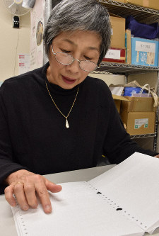 Shizuyo Suzuki, who works as a volunteer, touches a paper to review what she transcribed into braille. (Mainichi/Mirai Nagira)