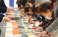 天皇陛下の在位30年を祝って記帳する人たち=皇居で2019年2月24日午前9時46分、宮武祐希撮影
