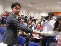 県民投票の成果に「辺野古」県民投票の会のメンバーと握手する元山仁士郎代表(左)=那覇市で2019年2月24日午後8時48分、上入来尚撮影