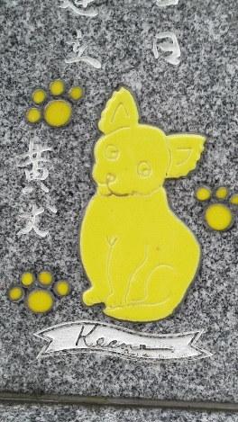 自宅そばに建てた墓石の背面にも、「黄犬(キーン)」がかわいい顔を見せている。幼い頃に米ニューヨークで飼っていたスピッツを模したもの=2014年10月21日、中澤雄大撮影