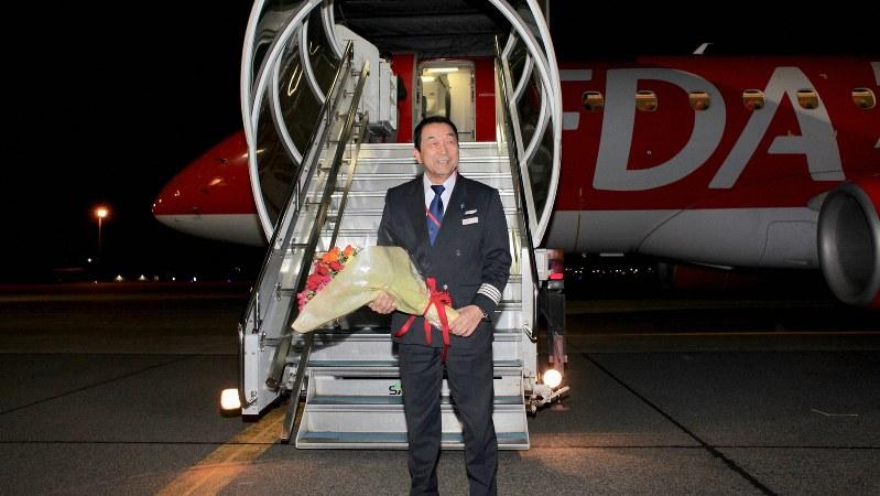 ラストフライトを終えて花束を受け取る秋田芳男さん(フジドリームエアラインズ提供)