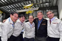 Yuichi Tsuda, project manager of the Japan Aerospace Exploration Agency's Hayabusa2 space probe, center, and other team members pose for a commemorative photograph in front of a model of the explorer in Chuo Ward of Sagamihara, Kanagawa Prefecture, southwest of Tokyo, on Feb. 22, 2019, after the probe successfully touched down on the asteroid Ryugu. (Mainichi/Naoki Watanabe)