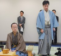 対局室に入る久保利明王将(右)。左は挑戦者の渡辺明棋王=那覇市で2019年2月25日午前8時49分、上入来尚撮影