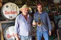 手作りカシャッサを手にするルイス・ナタウ・ザンドナさん(左)と次男ペドロ・ルイスさん=ブラジル南東部ブラガンサパウリスタで2019年2月5日、山本太一撮影