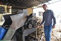 カシャッサの原料となるサトウキビを搾る機械の調子をみるペドロ・ルイスさん=ブラジル南東部ブラガンサパウリスタで2019年2月5日、山本太一撮影